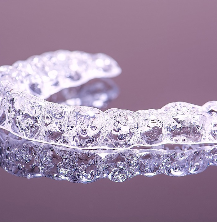 Clear orthodontic aligner on purple background.