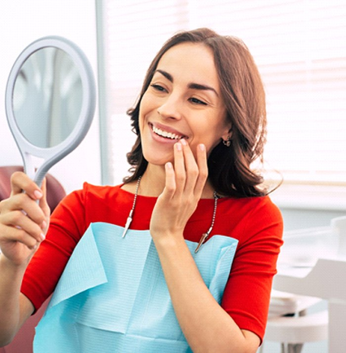 Woman with straight teeth smiling into hand mirror