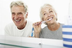 senior couple laughing brushing teeth