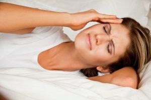 Woman waking with a headache.