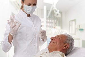 Dental hygienist talking to senior patient in dental chair