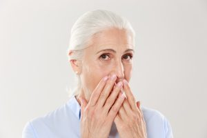 older woman covering mouth in shame
