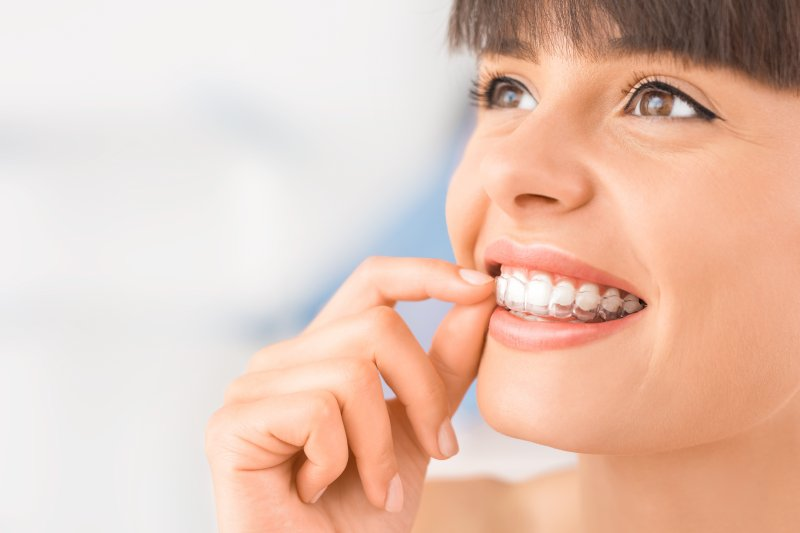 a young woman removes her Invisalign aligner during treatment